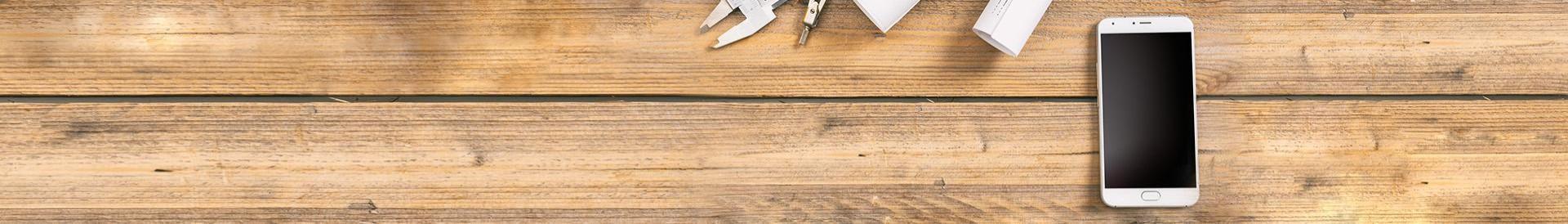 Biały smartfon na drewnianym stole obok narzędzi projektowych